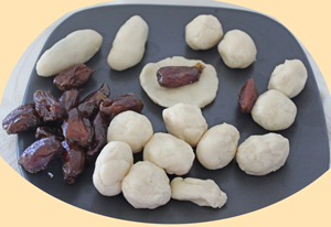 Ball of dough, dates and dates being enclosed in dough